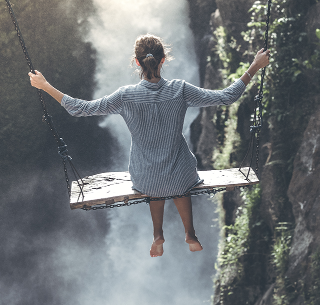 Woman on a swing over a gorge contemplating her risk