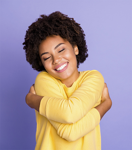 Lovely young Black woman hugging herself, smiling